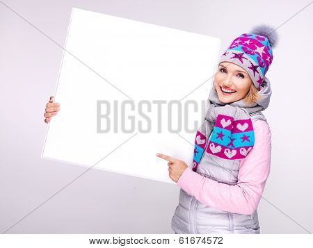 Adult smiling  woman in warm outerwear  holds the white banner in hands and points on it