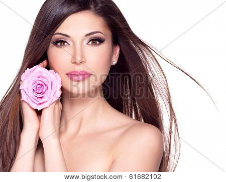 Portrait of a beautiful white pretty woman with long straight hair and pink rose at face.