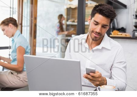 Young man using laptop and mobile phone in the coffee shop
