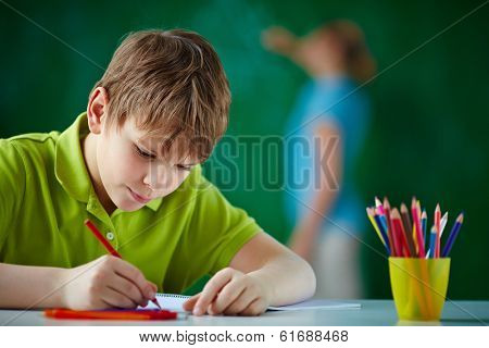 Portrait of cute schoolboy drawing with colorful pencils