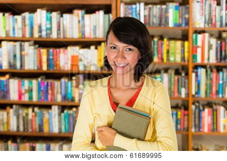 Student - a young woman or girl learning in a library, she proudly holds a couple of books and smiling