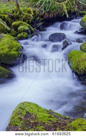 Waterfall with mossy rocks and soft water flow