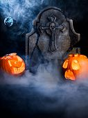 image of tombstone  - Angry face and scared face of Halloween pumpkins with moon tombstone and bat on misty dark background - JPG
