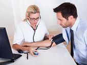 pic of sphygmomanometer  - Attractive young female doctor or nurse taking a male patients blood pressure using a sphygmomanometer - JPG