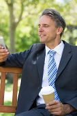 Mature businessman using cellphone while holding disposable coffee cup at park