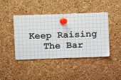 stock photo of goal setting  - The phrase Keep Raising the Bar on a piece of graph paper pinned to a cork notice board - JPG