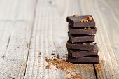 stock photo of wood pieces  - Pile of chocolate pieces with cocoa on wooden background - JPG