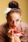 stock photo of flirtatious  - Portrait beautiful seductive woman fashion girl retro style holding red chilli pepper - JPG