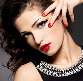 Beauty fashion woman with red nails, lips and golden eye makeup  - on black background