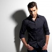 stock photo of enticing  - Fashion portrait of young man in black shirt poses over wall with contrast shadows - JPG