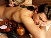 image of stone-therapy  - Handsome man having stone massage in spa salon - JPG