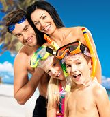 stock photo of mask  - Portrait of  happy fun beautiful family with two children at tropical beach with protective swimming mask - JPG