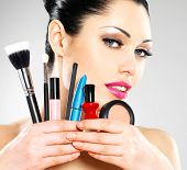 stock photo of face-powder  - Beautiful woman with makeup brushes near her face - JPG
