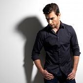 image of enticing  - Fashion portrait of young man in black shirt poses over wall with contrast shadows - JPG