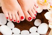 stock photo of pedicure  - Closeup photo of a beautiful female feet with red pedicure - JPG