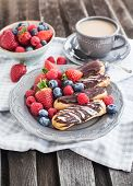 stock photo of eclairs  - Chocolate eclairs and fresh berries on plate with cup of coffee on the background - JPG
