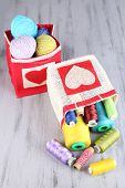 picture of lurex  - Bags with bobbins of colorful thread and woolen balls on wooden background - JPG