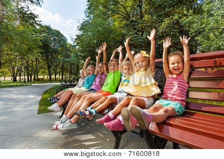 Group of kids on the bench cheering lifting hands