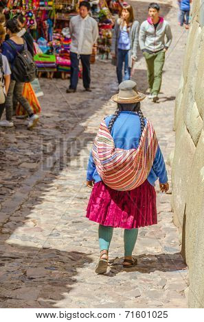 CUZCO, PERU, MAY 1, 2014: Local woman in folk costume with a Manta, which is a traditional carrying cloth, walks down a commercial street with souvenirs and craft stores