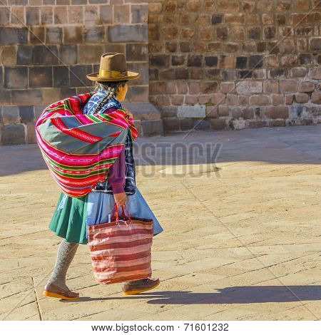 CUZCO, PERU, MAY 1, 2014: CUZCO, PERU, MAY 1, 2014: Local woman in folk attire with a Manta, which is a traditional carrying cloth, walks by Basilica Menor de la Merced