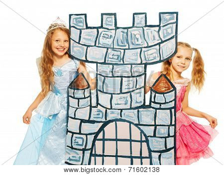 Two princesses behind cardboard castle tower