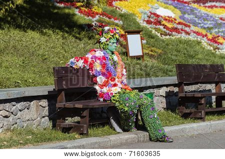man in hand made costume from flowers in park