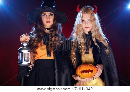 Two girls with lantern and pumpkin looking at camera