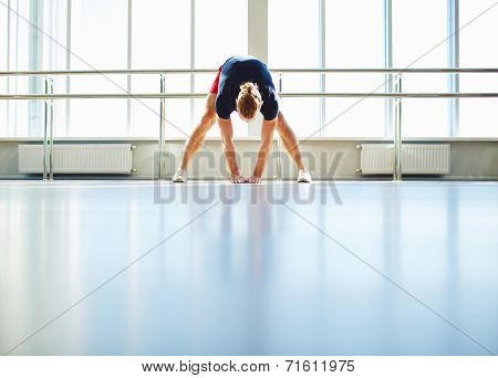 Sporty man in activewear doing physical exercises in gym