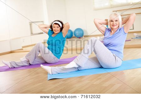 Two active females doing physical exercise in sport gym