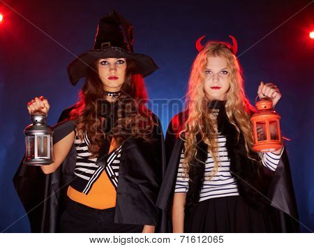Blond and brunette females with lanterns looking at camera in the dark