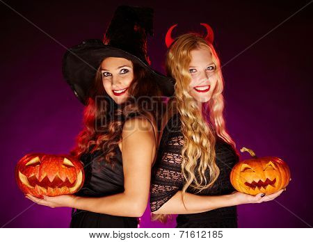 Two happy females with jack-o-lanterns looking at camera with smiles