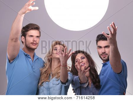 casual group of people reaching out for a big ball of light to tell them their future
