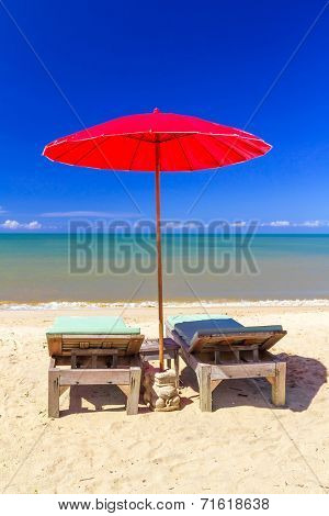 Red parasol with deckchair on tropical beach in Thailand