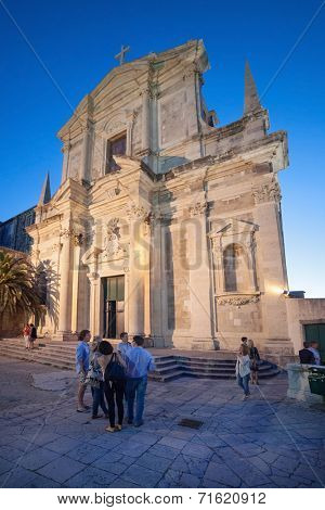 DUBROVNIK, CROATIA - MAY 26, 2014: Night shoot of people in front of Jesuit Church of St. Ignatius. The church belfry houses the oldest bell in Dubrovnik, cast in 1355 by Viventius and his son Viator.