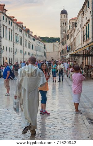 DUBROVNIK, CROATIA - MAY 26, 2014: Tourists walking on Stradun at sunset. Stradun is 300 meters long main pedestrian street in Dubrovnik.