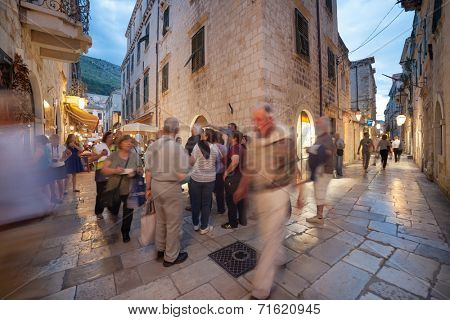 DUBROVNIK, CROATIA - MAY 27, 2014: Night shot of group of tourists on city streets. Dubrovnik is one of the prominent tourist destinations in the Mediterranean.
