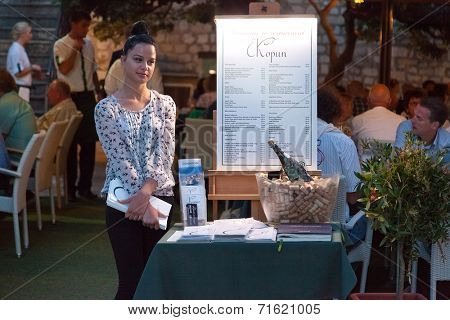 DUBROVNIK, CROATIA - MAY 28, 2014: Restaurant Kopun's hostess standing in front of the entrance. Dubrovnik has many restaurants which offer traditional Dalmatian cuisine and some great wine lists.
