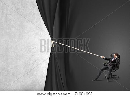 Young businessman sitting in chair and pulling curtain with rope