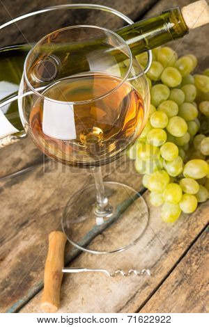 Wineglass With White Wine, Botlle, Corkscrew And Cluster Of Grapes Around On Wood Background