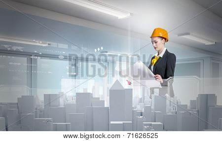 Young woman in hardhat examining construction project