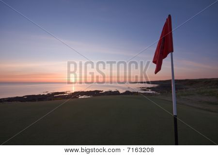 Red Golf Flag On A Coastal Course At Sunrise