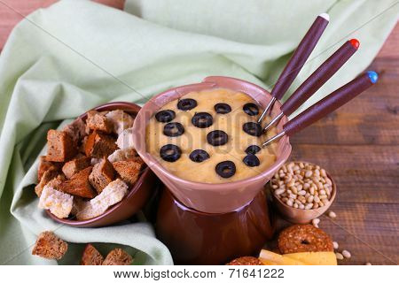 Fondue, olives, rusks and spices on napkin on wooden background