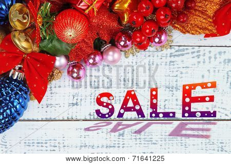 Concept of discount. Christmas toys and decoration on wooden table close-up