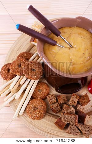 Fondue, biscuits, and rusks on cutting board on wooden background