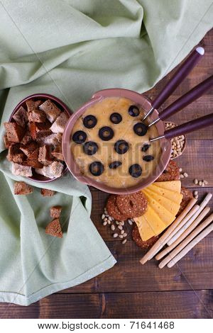 Fondue, olives, slices of cheese, rusks and spices on napkin on wooden background
