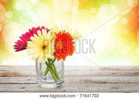 Colorful gerbera flowers on wooden table with autumn sunny bokeh