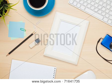 Photo frame on office table with notepad, computer and camera. View from above