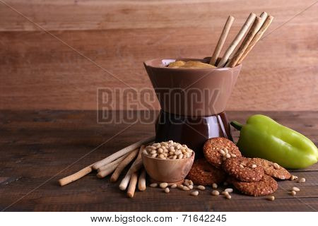 Fondue, spice, biscuits and pepper on wooden background