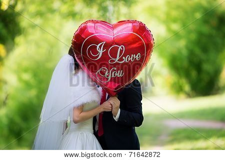 The Bride And Groom In The Park With The Red Balloon With The Words