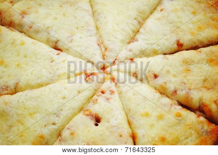Close-up Of The Center Of A Sliced Cheesy Pizza